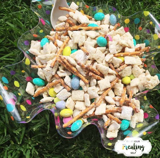 White Chocolate coated chex cereal mixed up with pretzel sticks and M&Ms makes this Easter Bunny Chow Recipe thats sure to be a sweet, snacky hit with everyone at the table!