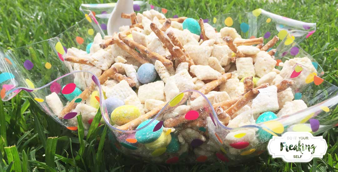 White Chocolate coated chex cereal mixed up with pretzel sticks and M&Ms makes Easter Bunny Chow thats sure to be a sweet, snacky hit with everyone at the table!
