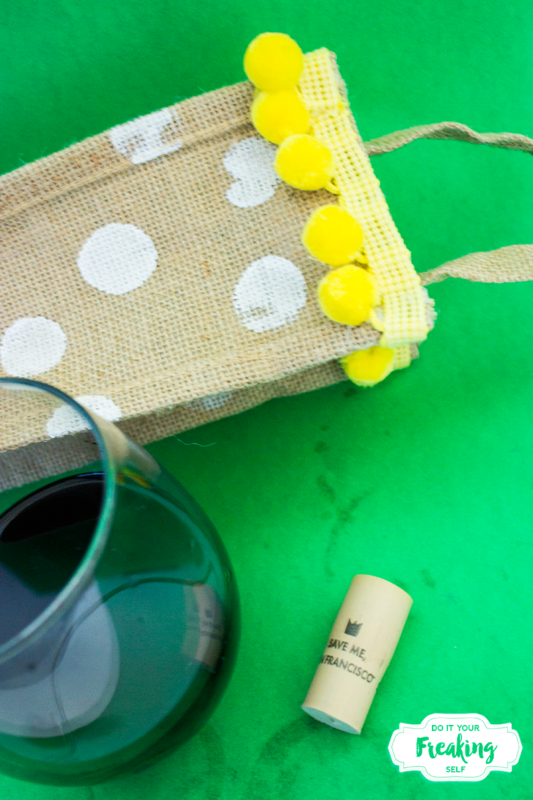 Dress up your wine with this pom pom trimmed DIY New Sew Wine Gift Bag! Easy beginner craft to do in 30 minutes or less. Classy and festive for summer parties!