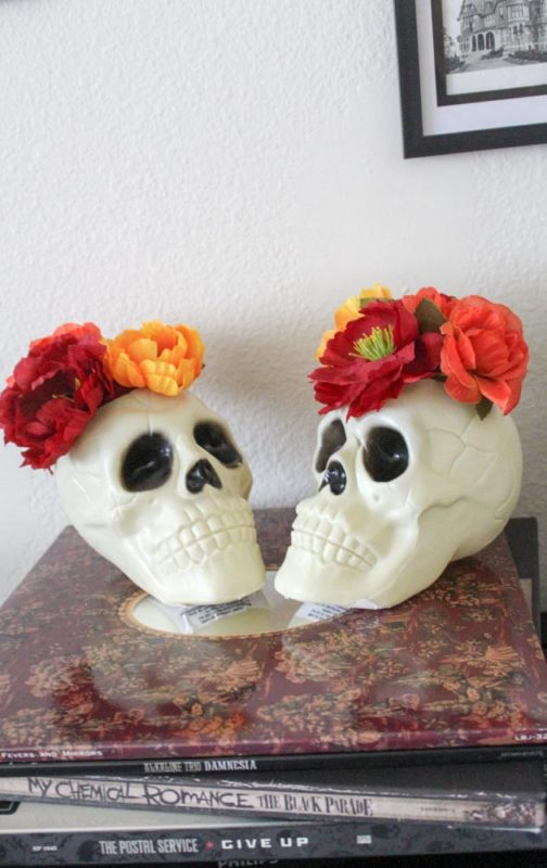 Make a DIY Skull Vase in under 5 minutes! Just cut a hole in the top of a plastic skull and fill with fake flowers!