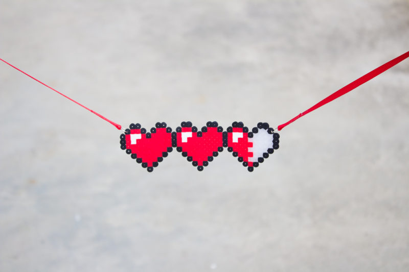 Let your geek flag fly with a DIY Legend of Zelda Pixel Heart Statement Necklace. Pull out some perler beads and your nintendo and party like it's 1986.