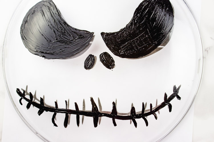 Scare up a good treat by making a simple DIY Jack Skellington Cake stand! Perfect for your Halloween decor or party tablescape! Dollar Store DIY! - Nightmare Before Christmas | Tim Burton | Food Safe | Halloween Projects | Party table - Doityourfreakingself.com