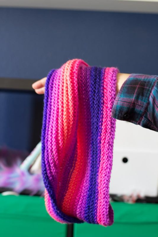 Knit with straight needles, this knit gradient cowl scarf is perfect for beginner knitters learning new stitches. Grab your favorite yarn and get knitting!